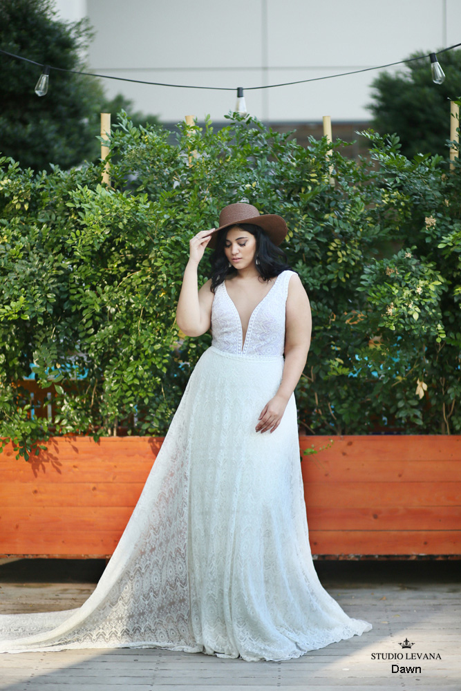 A woman wears a flowy wedding dress and wide brim hat